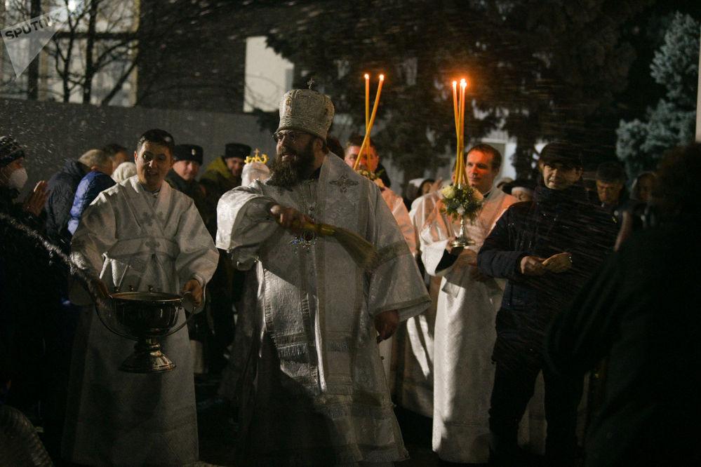 Священнослужитель окропляет верующих святой водой во время Крещение Господне в Свято-Воскресенском кафедральном соборе в Бишкеке
