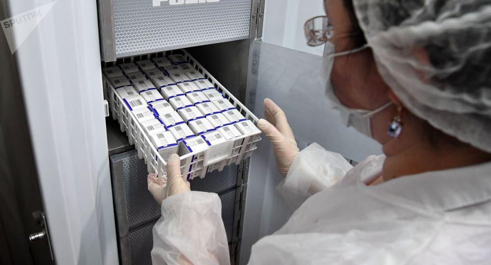 Медработник достает из холодильника вакцину Спутник V