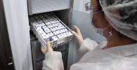 Муздаткычтан Спутник V вакцинасын чыгарып жаткан лаборатория кызматкери. Архив