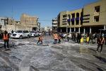Рабочие очищают место двойного теракта на центральном рынке в Багдаде, Ирак. 21 января 2021 года
