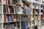 Девушка выбирает книги в библиотеке. Архивное фото