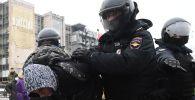 Сотрудники правоохранительных органов задерживают участника несанкционированной акции сторонников Алексея Навального в Москве.