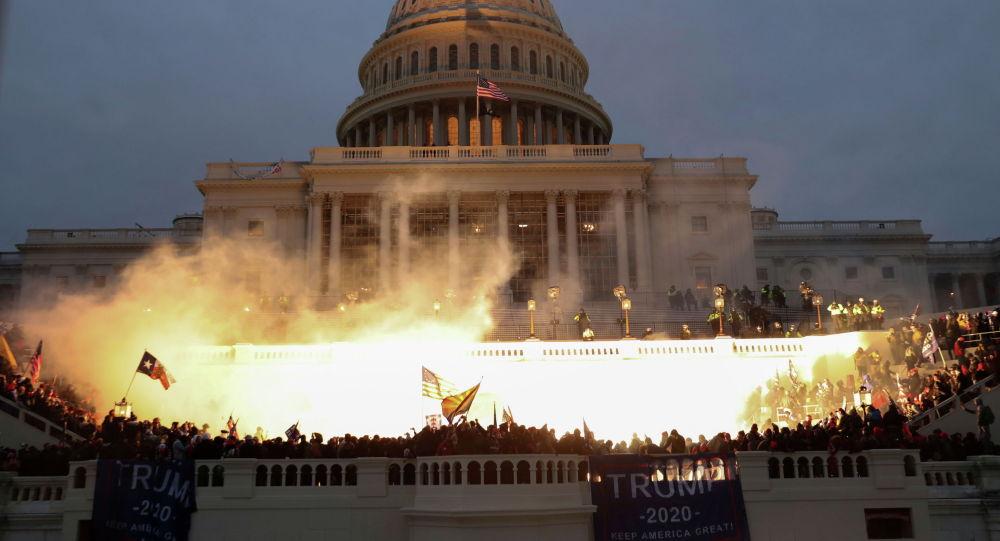 Взрыв, вызванный полицейским боеприпасом, виден, когда сторонники президента США Дональда Трампа собираются перед зданием Капитолия США в Вашингтоне. США, 6 января 2021 года