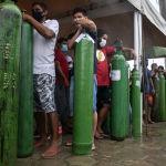 Люди стоят в очереди в бразильском городе Манаус, чтобы заполнить баллоны кислородом, для своих родных инфицированных COVID-19. 19 января 2021 года