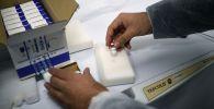 Мужчина держит вакцину Спутник V. Архивное фото
