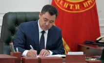 Президент Кыргызстана Садыр Жапаров подписывает документ. Архивное фото