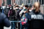 Сотрудники полиции наблюдают за очередью людей в масках у центра вакцинации в здании Берлинской арены