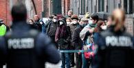 Берлиндеги Аренадагы эмдөө борборунун алдында кезекте турган беткапчан кишилерди полиция кызматкерлери карап турат