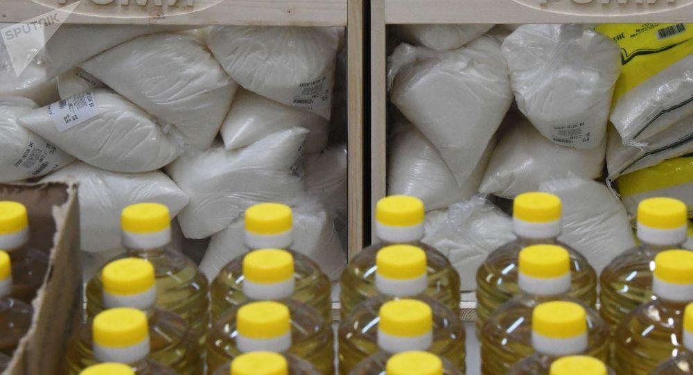 Мешки с сахаром и бутылки растительного масла на прилавке магазина. Архивное фото