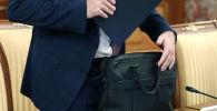 Чиновник кладет документы в портфель. Архивное фото