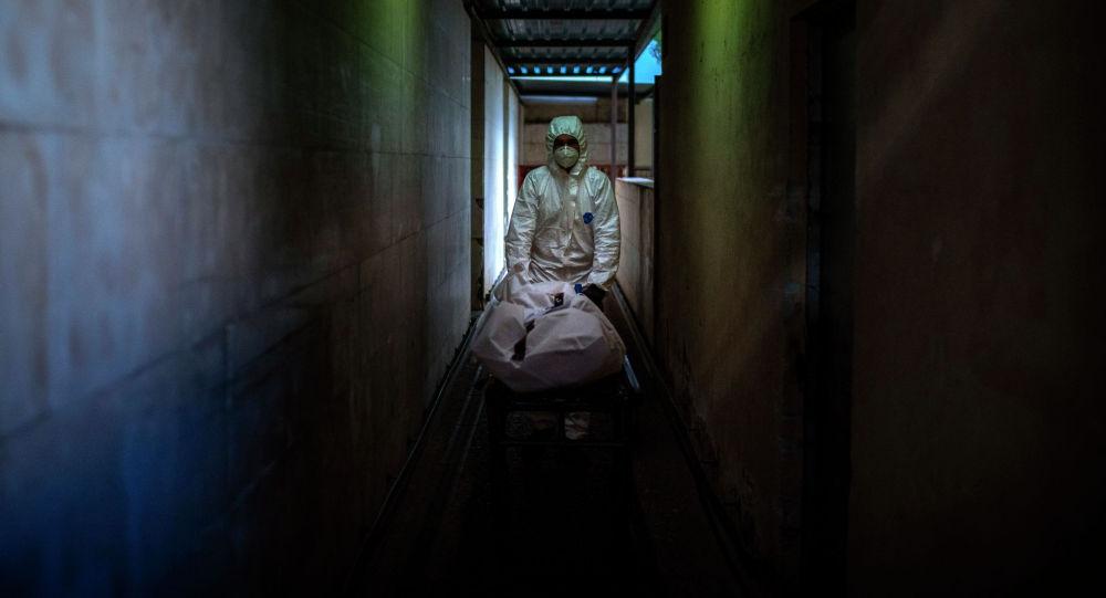 Работник морга переносят тело жертвы COVID-19. Архивное фото