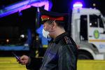 Сотрудник полиции в защитной маске держит смартфон. Архивное фото