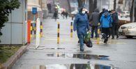 Женщина идет по тротуару на проспекте Чуй во время дождя в Бишкеке. Архивное фото