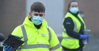 Работник в специальной куртке с набором для тестирования на коронавирус в Уолсолле (Англия)