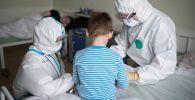 Врачи с пациентом в больнице где проходят лечение дети с COVID-19. Архивное фото