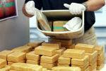 Офицер полиции Германии показывает изъятые упаковки с героином. Архивное фото