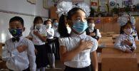 Кыргызские школьники одетые в защитные маски на уроке в школе. Архивное фото
