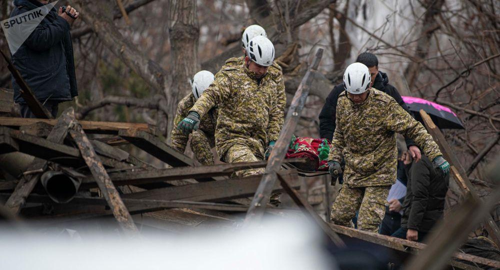 Сотрудники МЧС выносят тело погибшего при взрыве газа в частом доме в Аламединском районе Бишкека