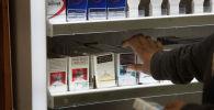 Владелец магазина достает упаковку сигарет. Архивное фото