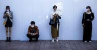 Жители Токио стоят соблюдая санитарную дистанцию. Архивное фото