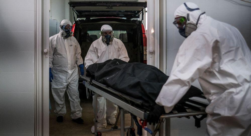 Работники похоронного агентства в СИЗах перевозят тело жертвы COVID-19. Архивное фото