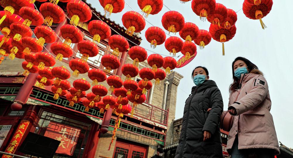 Женщины в медицинских масках гуляют под красными фонарями возле озера Хоухай в Пекине