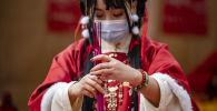 Салттуу кийимчен аялдын Япониядагы Ма Чжу Мяо чиркөөсүндө сыйынып жаткан учуру