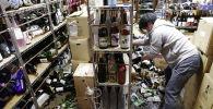 Сотрудник винного магазина среди разбитых бутылок после сильного землетрясения в Фукусиме. (Япония) 13 февраля 2021 года