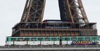 Надземный парижский метро проходит над мостом Пон-де-Бир-Хакейм рядом с Эйфелевой башней в Париже