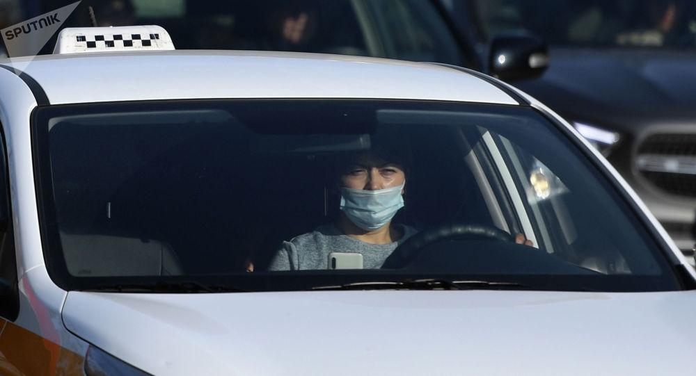 Водитель в защитной маске за рулем такси на одной из улиц в Москве. Архивное фото