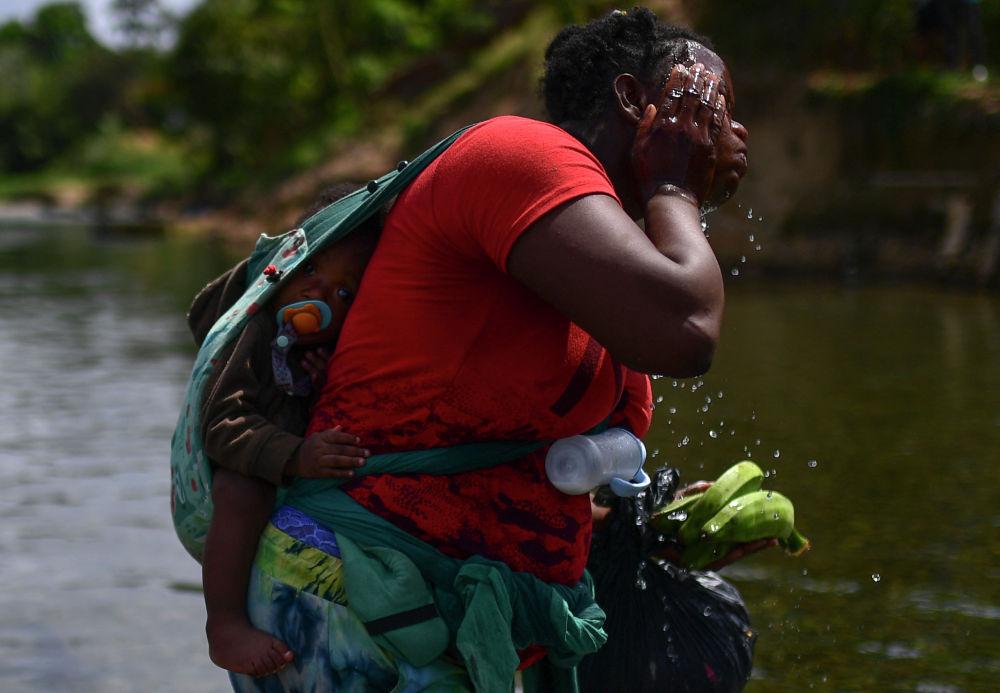 Женщина с ребенком переходят реку Чукунаке в Панаме во время пути в США. 10 февраля 2021