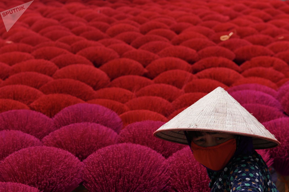 Женщина обрабатывает сушеные ароматические палочки в преддверии празднования Лунного Нового года во Вьетнаме. 3 февраля 2021 года
