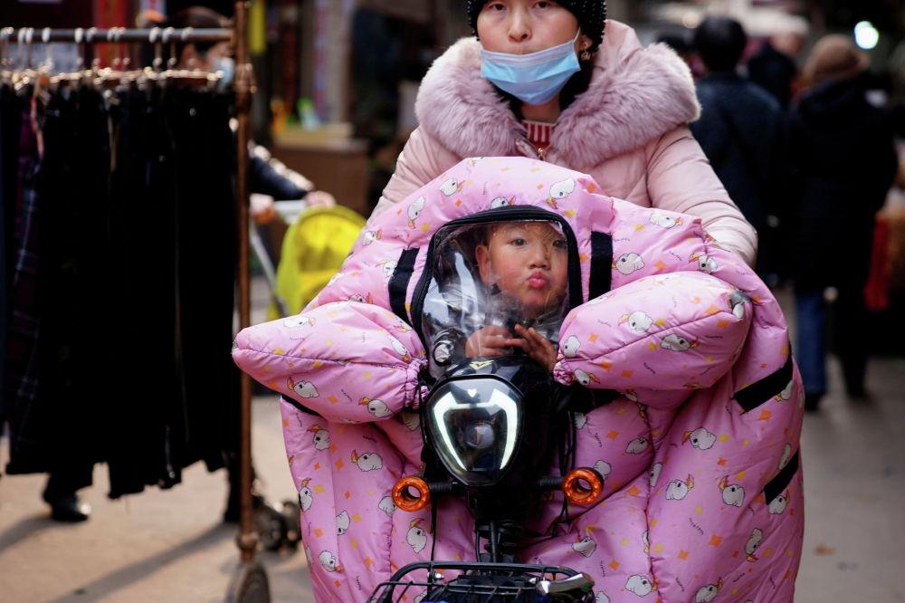 Мать с ребенком едут на велосипеде на одной из улиц китайского города Ухань. 8 февраля 2021 года
