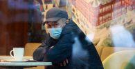 Мужчина в медицинской маске в кафе. Архивное фото