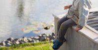 Мальчик сидит на берегу водоема. Архивное фото