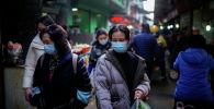 Люди в масках на уличном рынке после вспышки COVID-19 в Ухане