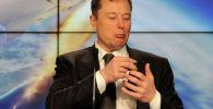 Основатель SpaceX Илон Маск смотрит в свой мобильный телефон. Архивное фото