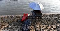 Янцзы дарыясынын жээгинде балык уулап жаткан адам. Архив