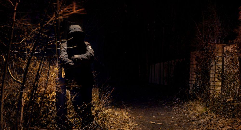 Мужчина в капюшоне на улице возле фонарного столба. Иллюстративное фото