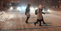 Люди переходят дорогу во врем метели