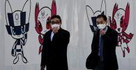 Мужчины в защитных масках на фоне талисмана Олимпийских игр 2020 в Токио (Япония)