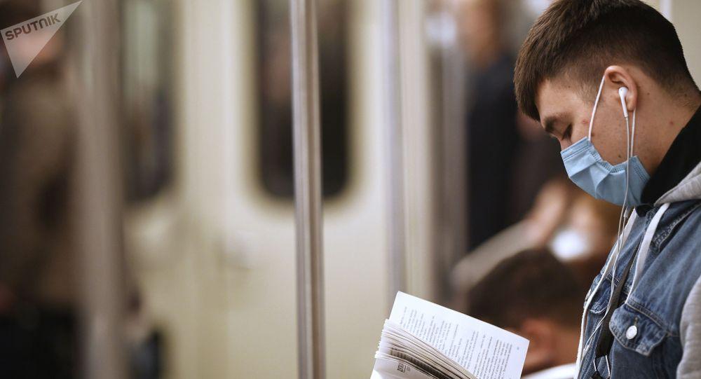 Коомдун траспортто китеп окуп бараткан адам. Архив
