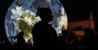 Женщина в маске стоит перед огромным надувным глобусом в Праге
