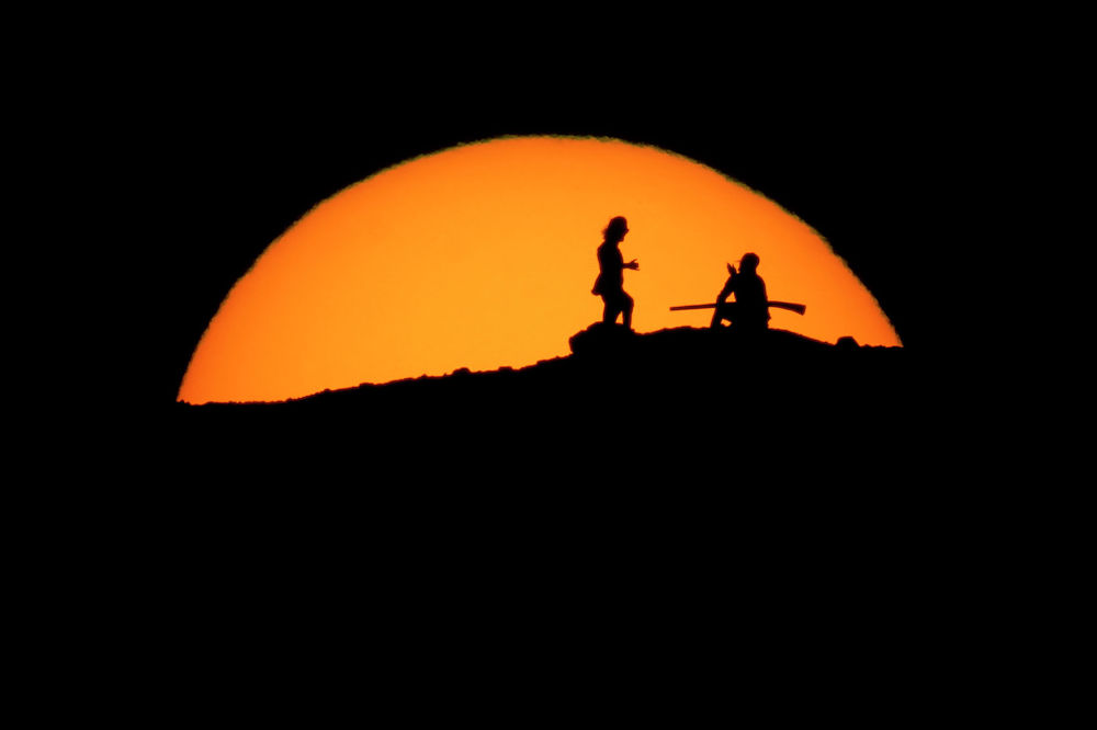 АКШнын Аризона штатынын Финикс шаарындагы Папагайо паркындагы чокудан саякатчылар күндүн батып бара жатканын карап турушат
