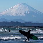 Фудзисавада (Япония) Фудзи тоосунун тушунда пляждан чыгып бара жаткан серфинг оюнчусу