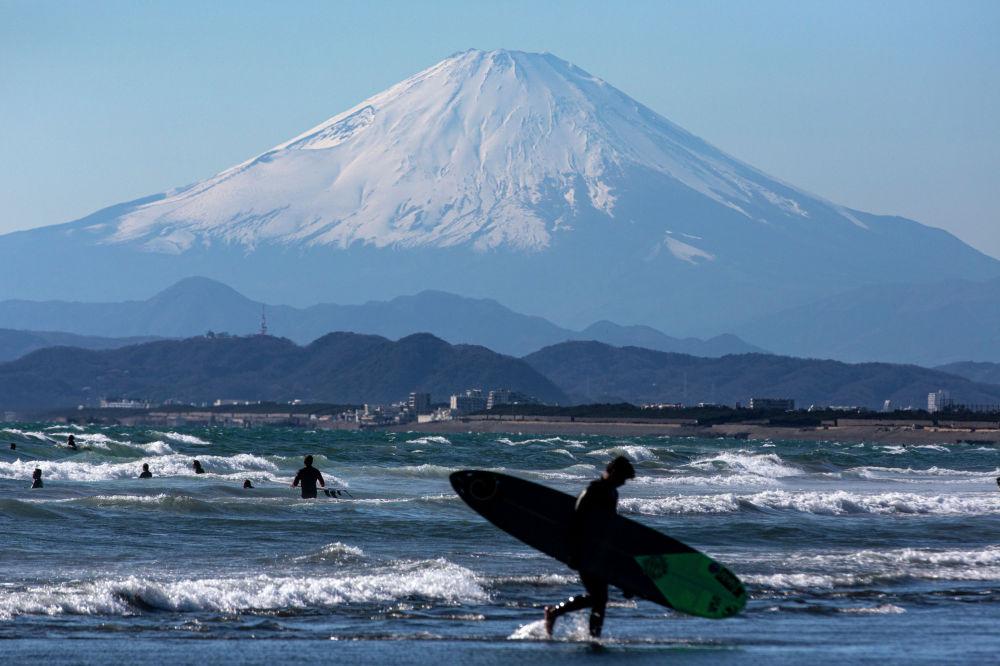 Серфер уходит с пляжа на фоне горы Фудзи, в Фудзисаве, к западу от Токио (Япония)
