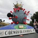 Коргоочу маска кийген аял Ниццада (Франция) коронавирустун жаңы сүрөтүн чагылдырган карнавал аянтчаны сүрөткө тартып жатат