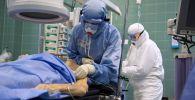Медицинские работники и пациент c COVID-19 в отделении реанимации больницы