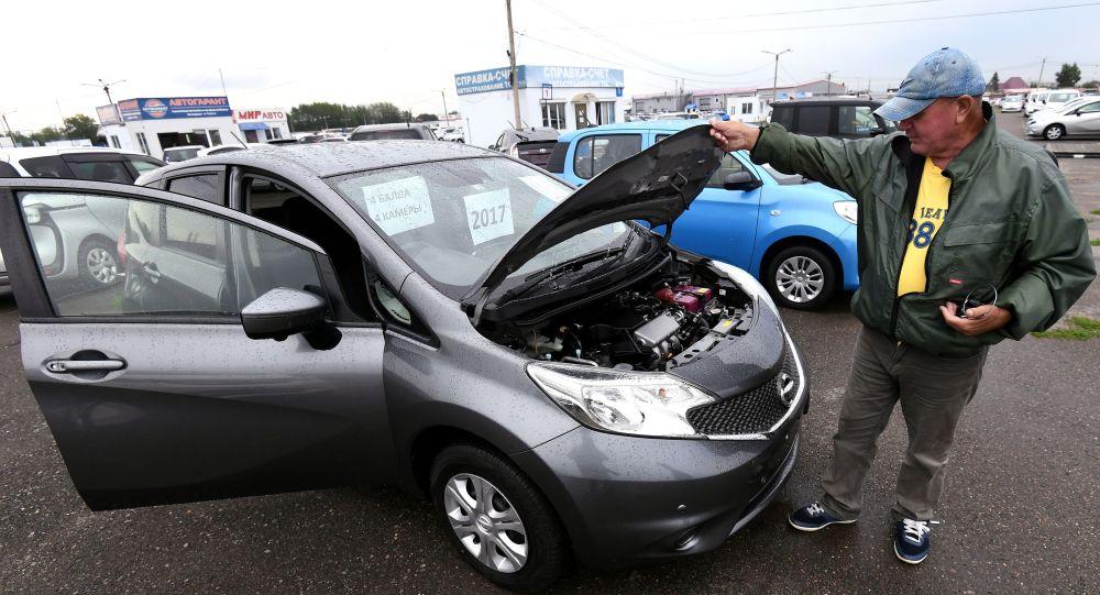 Продавец показывает праворульный хэтчбек выставленный на продажу на рынке подержанных автомобилей. Архивное фото