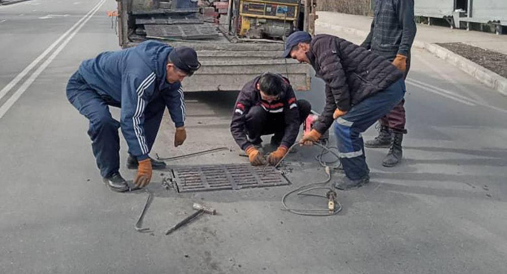 Сотрудники МП Бишкекасфальтсервис закрывают открытый люк в Бишкеке